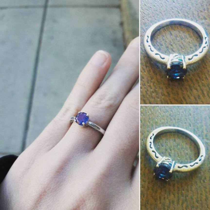 Picture of my engagement ring. The stone is a color-shifting blue/green/purple. There are little swirly cutouts on the band.