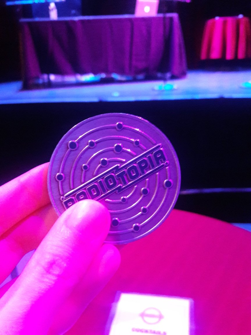 Photo of my Radiotopia challenge coin in front of the 99% Allusional stage.