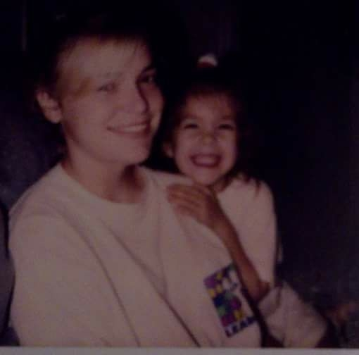 Image of me (age 4-5) with my cousin (She's probably 15?). I'm CHEESING.