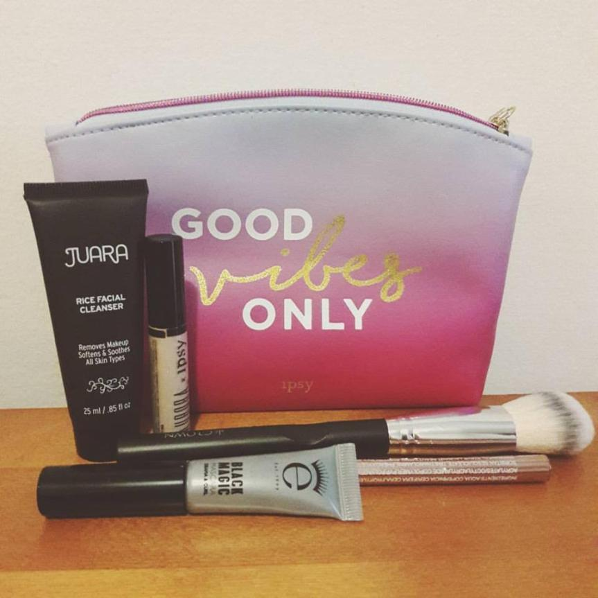 "Image of my ipsy bag and the contents. The bag has a light blue to pink gradient and says ""GOOD VIBES ONLY"""