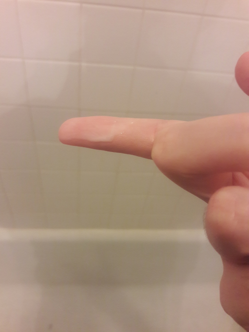 Image of the serum for the Manefit Beauty Planner Mask in Lily, shown on my finger. It's thin and milky white. Yum.