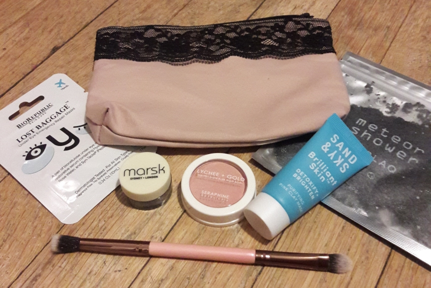 Image of the February 2018 ipsy bag and contents. The bag itself is a light, light pink with a black lace trim.