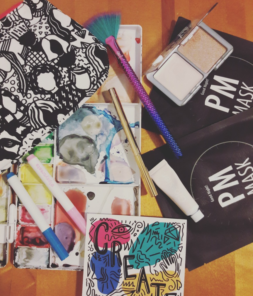 Image of the March 2018 ipsy bag and contents. I've done a flat lay on my messy watercolor palette to keep with the theme. This month's bag is a black and white drawing of women. They sent two markers so I could color it in. I didn't.