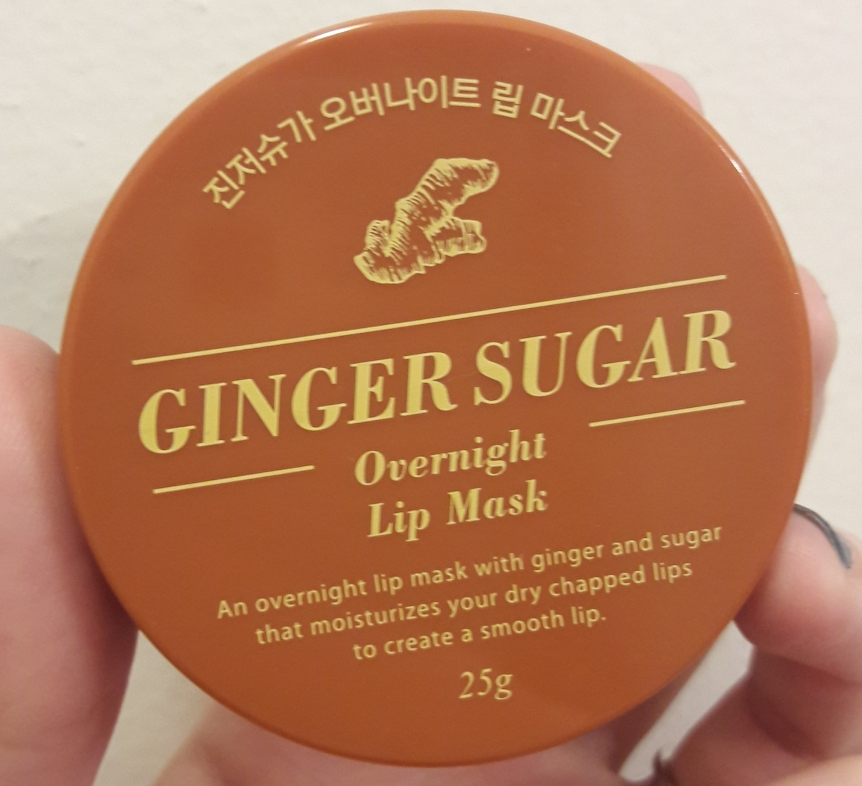 "Top view of the container. It says ""Ginger Sugar Overnight Lip Mask. An overnight lip mask with ginger and sugar that moisturizes your dry chapped lips to create a smooth lip."""