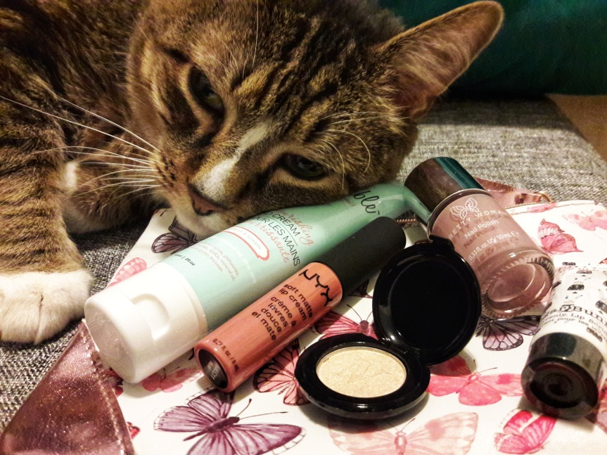 Picture of my April 2018 ipsy bag and contents. Baker (my cat) came over to nuzzle things because he can't stand not being the center of attention. This month's bag is white and covered in pink/purple butterflies with pink foil corners.
