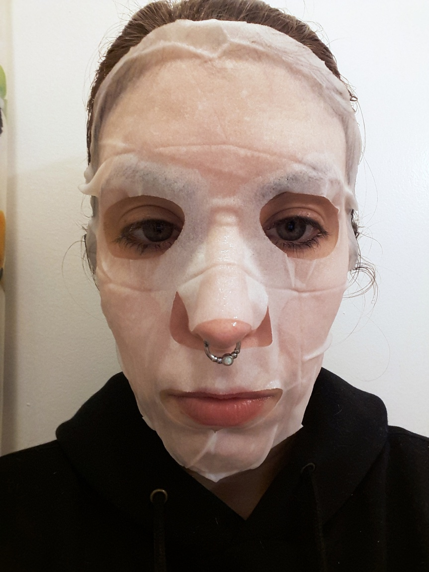 An unflattering picture of me wearing the sheet mask. I've got my giant weekend septum ring in.