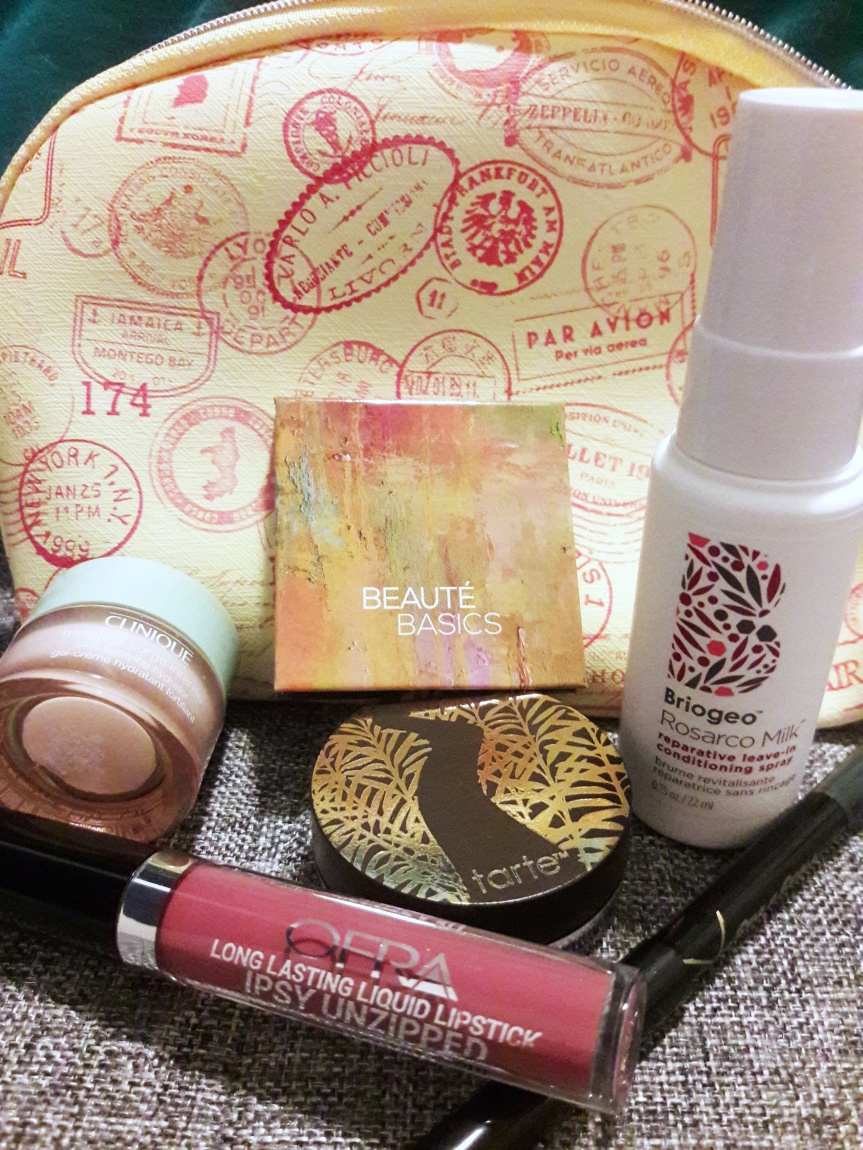 May 2018 ipsy bag and contents. The bag is a light yellow with an orange-y red passport stamp pattern.