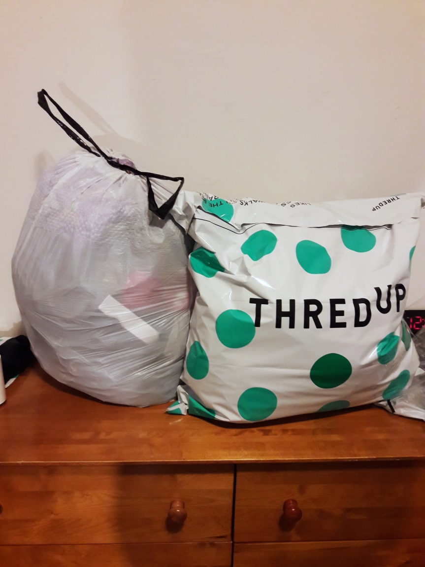The same clothes, but now half of them are in a thredUP bag with green polka dots.