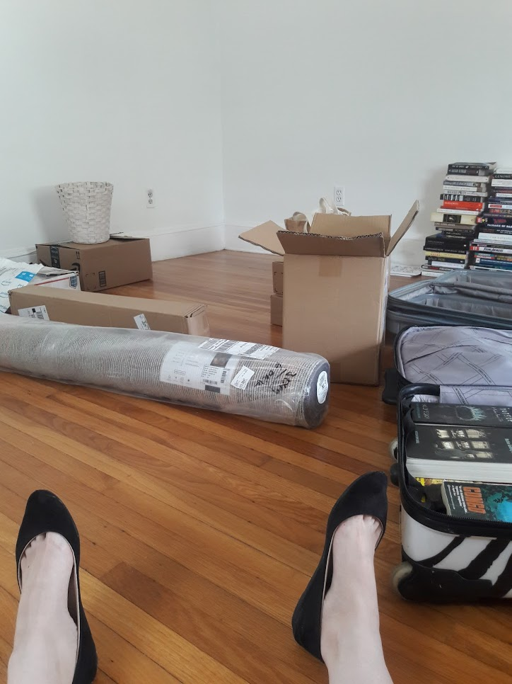 I'm sitting on the floor but only my feet are in the frame. I'm in my empty new living room surrounded by a few boxes and stacks and stacks of books.